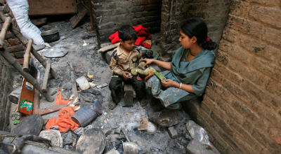 A Pakistani Christian sits with her son in her damaged house after it was burnt by mob a day earlier in Badami Bagh, Lahore on Sunday. (Reuters/Mani Rana)