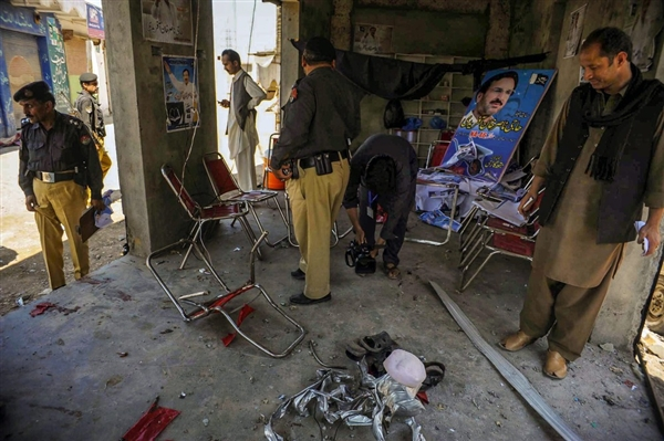 Pakistani police officers inspect the election campaign office of independent candidate Waris Afridi, after a bomb explosion on the outskirts of Peshawar.