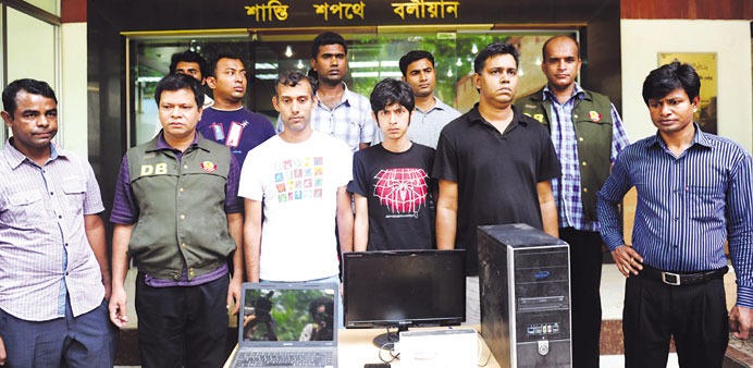 Police officials pose with three bloggers, centre, during a press conference in Dhaka yesterday.
