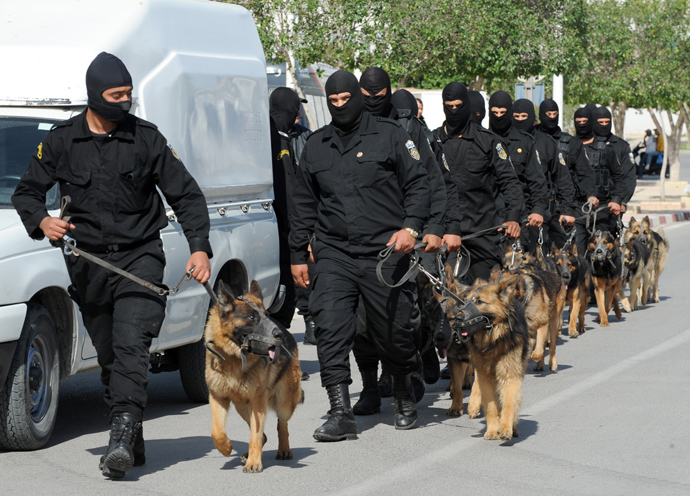 Tunisian Police Special Unit agents with dogs patrol in a street that leads to Okba Ibn Nafaa mosque in the central Tunisian city of Kairouan on May 19, 2013 (AFP Photo / Fethi Belaid)