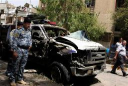 Security forces inspect the scene of a car bomb attack in the commercial area of Karradah in Baghdad, Iraq, Thursday, May 30, 2013. A series of morning bomb explosions in Baghdad and the northern Iraqi city of Mosul on Thursday, killed and wounded dozens of people, police said, in the latest eruption of violence rattling the country.