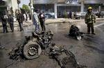An Afghan fireman stands next to the debris of a car at the scene where a suicide car bomber attacked a NATO convoy in Kabul, Afghanistan, Thursday, May 16, 2013. A Muslim militant group, Hizb-e-Islami,...