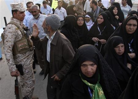 Iranian Shi'ite Muslim pilgrims walk past a member of Iraq's security personnel in Kerbala, 110 km (70 miles) south of Baghdad, June 7, 2013.