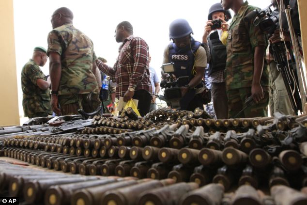 Banned: Journalists look at arms and ammunition which military commanders say they seized from Islamic fighters, in Maiduguri, Nigeria. Boko Haram, the radical group that once attacked only government institutions and security forces, is increasingly targeting civilians