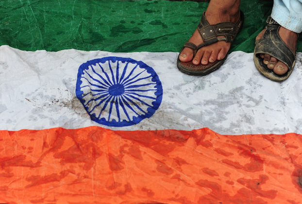 Supporters of Pakistan's hardline Jamaatud Dawa (JuD) stand on a India flag during a protest in Karachi on August 14, 2014. PHOTO: AFP