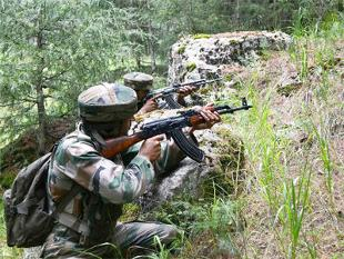 Army soldiers take position near the site of an encounter with militants at Hafrada forest area of Handwara North Kashmir's frontier Kupwara district.