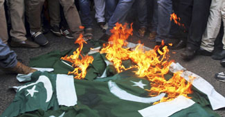 Supporters of India's main opposition Bharatiya Janata Party (BJP) burn Pakistani flags during a protest in Ahmadabad, India, Thursday, Aug. 8, 2013.