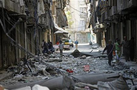 Residents walk on rubble in a damaged street in Aleppo's district of Bustan al-Basha September 8, 2012. REUTERS/Zain Karam