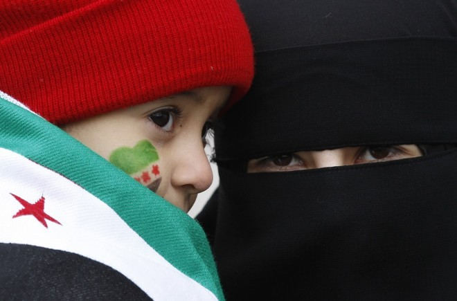 A Syrian mother and girl, her face painted with the colours of the Syrian independence flag, attends a protest against President Bashar Al-AssadReuters